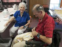 Carol Edwards helps Carlton Marshall with a dress he is making for his granddaughter during an adult sewing class in Ovilla.
