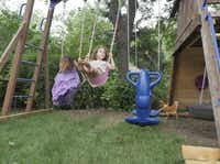 A chicken darts past as Sullivanne Smith, 4 (left), and Gentry Smith, 5, swing in the Smiths' backyard, where their father also grows vegetables for their meals.Ron Baselice  -  Staff Photographer