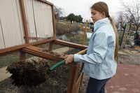Volunteer Emma Livingston turns a compost pile at Plano Environmental Education Center in Plano.