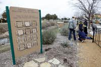 Volunteers pull weeds near a sign about compost critters at Plano Environmental Education Center in Plano.