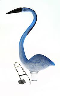 A long-necked water bird, made in China of glass, is boxed with a stand to anchor it in the ground on in a large flower pot. $89.99 at Calloway's, multiple locations.