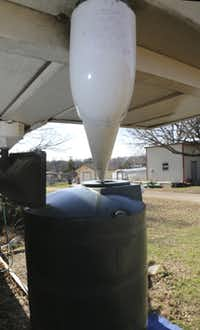PVC tubing moves rainwater from the roof gutter to a 500-gallon container on Brad Ackerman's property.