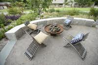 Crushed-granite sand composes the floor of the seating area around the rusted-steel fire pit. Behind the stone retaining wall, the lot drops about 12 feet to the street.