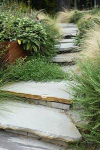 A flagstone walkway leads visitors through the garden from street level to the front door.
