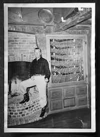 This vintage photo shows original owner Ted Dealey posing by his gun case in the living room of the home.