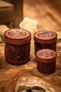 Store those essentials in leather-tooled canisters. $129, set of three, at Antiques Curated, Dallas.(Ben Garrett - Anteks Curated)