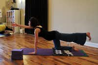 """Amanda Heller, 21, 28 weeks pregnant, does a """"cat with tail"""" posture during a prenatal yoga class, on March 15, 2012 at the Pranaa yoga studio in Plano."""
