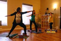 L-R: Shakira Gbetibouo, 34, 32 weeks pregnant, Tamra Pierce, 29, 18 weeks pregnant, and Lisa Stropnicky, 27, 9 months pregnant, during a strong, confident, peaceful, warrior mama pose at a prenatal yoga class, on March 15, 2012 at the Pranaa yoga studio in Plano.