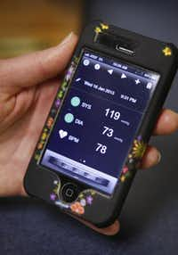 Registered Dietitian Susan Rodder, of Southwestern Medical Center, monitors her blood pressure with her iPhone, photographed January 29, 2013. She is using a Withings Smart Blood Pressure Monitor and app on her iPhone to check and keep track of her blood pressure. One of her readings is shown on the screen.