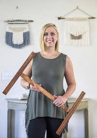Rebekah Wright poses for a photo with her loom in front of two woven wall hangings that she made(Ashley Landis - Staff Photographer)