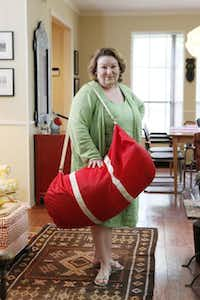 "Sheila Brenner with ""big red,"" a large tote bag she uses while traveling to collect items she later decorates her home with, on Thursday, June 06, 2014 in Dallas.Ben Torres  -  Special Contributor"
