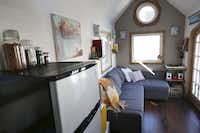 Left:  The living area of Randi and Cody Hennigan's tiny house includes a couch with storage and a corner for their record player and albums.  Right:  The steps to the loft (along the wall next to the refrigerator) have storage space for the couple's camping equipment.(Andy Jacobsohn - Staff Photographer)