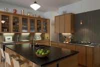 The kitchen has dark countertops and a mix of wood and glass fronts on the upper cabinets.