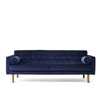 Jonathan Adler's Crescent Heights tufted sofa, in navy blue, is $2,895 at J. C. Penney.