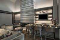 Serving as a dramatic focal point to a great room, a 20-foot tall fireplace of Striato Olimpico marble rises to the ceiling.(Dan Piassick - Allied Stone)