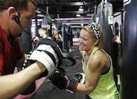 Boxing instructor Sean Holden  spars with Robin Malone of McKinney during a workout at Title Boxing Club in McKinney.(Vernon Bryant - Staff Photographer)