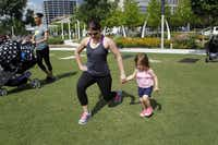 Hannah Miller, 22 months, tries to mimic the moves of her mother, Stephanie Miller, during Stroller Boot Camp.(Lara Solt - Staff Photographer)