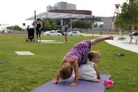 Siena, 3, and Thea Neri, 11 months, practice yoga while their mother, Lara Neri of Irving (background, right), exercises at Klyde Warren Park.(Lara Solt - Staff Photographer)