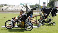 Audri Rojas, 15 months, munches on a snack as her mother, Veronica Rojas, works out at Klyde Warren Park's Stroller Boot Camp. The classes help moms connect with their kids and one another while adapting to a new routine.Photos by Lara Solt - Staff Photographer