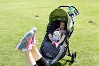 Hannah Miller, 22 months, enjoys a snack while her mother Stephanie Miller exercises at a Stroller Boot Camp class at Klyde Warren Park in Dallas on Tuesday, June 3, 2014.( Lara Solt  -  Staff Photographer )