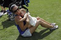 Lara Neri hugs her daughter, Thea Neri, 11 months, while exercising during a Stroller Boot Camp class at Klyde Warren Park in Dallas on Tuesday, June 3, 2014.( Lara Solt  -  Staff Photographer )