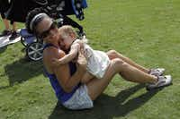 Lara Neri hugs her daughter, Thea Neri, 11 months, while exercising during a Stroller Boot Camp class at Klyde Warren Park in Dallas on Tuesday, June 3, 2014.Lara Solt  -  Staff Photographer