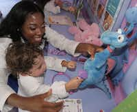 "Dr. Myiesha Taylor helps A.J. Vasquez, 2, of Fort Worth check a dragon's reflexes. In addition to an appearance on the Disney show ""Doc McStuffins,"" Taylor founded  the Artemis Medical Society for female doctors of color."