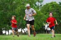 Micah Crownover, 7, and Noah Crownover, 10, run with their dad chaplain Matthew Crownover, 39, around the family's pond located behind their home, on May 12, 2012 in Sunnyvale, Texas. Crownover is a ultra-trail runner who runs several 50 and 100-mile races every year. His next race will be a 100 mile race in the mountains of New Mexico.