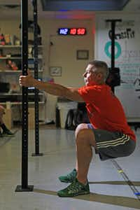 Mariotti says you can use doorknobs to anchor yourself while doing holding squats.