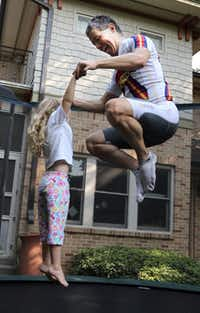 """Adams and daughter Trinity jump on the family's trampoline. """"If we jump 15 to 20 minutes five times a week, I'm having a hard workout and they're having a blast while we're laughing and talking."""""""