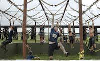 Racers pulled themselves along the Gorilla Ropes during the Original Mud Run on Saturday in Fort Worth.