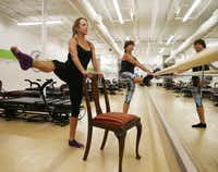"""Kerry McStay, left, and Elizabeth Lindberg demonstrate """"bare-bones workouts"""" using just an ordinary chair, especially good for people with financial, transportation, health or safety issues, at Studio 6 off of Preston Road and Forest Lane on Monday, October 14, 2013."""