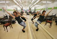 "Studio 6 Fitness owner Elizabeth Lindberg (left) and Kerry McStay demonstrate ""bare-bones workouts"" that can be done using a countertop or heavy piece of furniture instead of a barre at the gym."