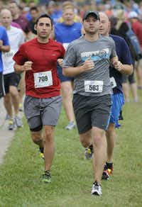 Bryan Delgado, left, and Aaron Lutz begin the the 10k race of the Tour des Fleurs behind the Dallas Arboretum on Saturday, Sep. 15, 2012.