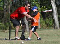 Former pro baseball player Drew Holder teaches proper batting hip alignment to Tristan Biggs, 7, at Bacchus Park in Frisco recently. Holder, who played with the Tri-City ValleyCats, Lexington Legends and Grand Prairie AirHogs, also has Type 1 diabetes and helps mentor Biggs with his diabetes.