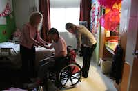 Rachel Herrera, 13, center, is helped by her mother Rebecca Herrera, left, and sister Amanda Herrera, 20, to sit on her wheel chair before attending occupational and physical therapy.