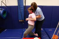 Rachel Herrera, 13, is helped to her feet by occupational therapist Liz Grant, right, after a session of therapy.