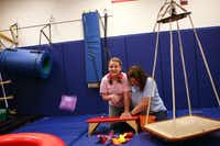 Rachel Herrera, 13, tosses a bean bag into a basket with the help of occupational therapist Liz Grant, right.
