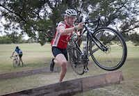 Chauncey Deller carries his bike over an obstacle during a training ride at Flag Pole Hill.( Rex C. Curry  -  Special Contributor )