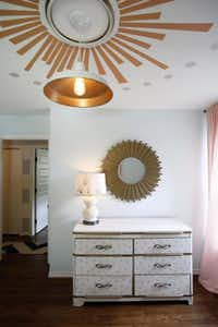 An old dresser, refurbished with polka dots, is the changing table. Giddens painted the sunburst design on the ceiling and found the sunburst mirror at Home Goods, which she repainted in metallic gold.(Lara Solt - Staff Photographer)