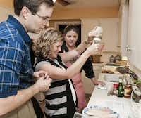 Brooke Green, center, prepares a marinade for tilapia under the watchful eye of registered dietician, Robin Plotkin, rear, as Brooke's husband Andy Green watches.