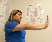 Brenda Alvarez demonstrates Step 5 of an arm exercise to alleviate hand pain.