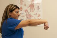 Brenda Alvarez demonstrates Step 8 of an arm exercise to alleviate hand pain.
