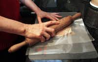 Carrie Brazeal of Lucas uses a rolling pin on wax paper to pound chicken breasts for Tuscan Chicken.