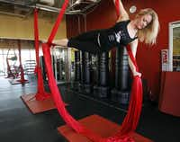 Kimberly McCarter demonstrates how to work out using the silks before a recent class at Power Play Fitness. The workout, which got a boost when Pink did a routine as part of her performance on the Grammy Awards show, involves climbing colorful silk ropes that hang from the ceiling.Mona Reeder - Staff Photographer