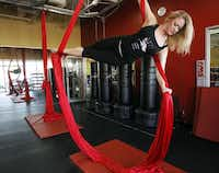 Kimberly McCarter demonstrates how to work out using the silks before a recent class at Power Play Fitness. The workout, which got a boost when Pink did a routine as part of her performance on the Grammy Awards show, involves climbing colorful silk ropes that hang from the ceiling.(Mona Reeder - Staff Photographer)