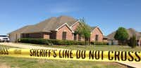 Crime scene tape wraps around the home of Kaufman County District Attorney Mike McLelland and his wife, Cynthia, near Forney. The two were found slain at the home Saturday.