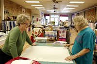 """Laura Murrey (left) and Cynthia McLelland lay out part of a quilt during a class in Kaufman. """"I use the creative arts to help get rid of tension,"""" McLelland said."""