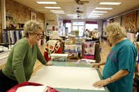 "Laura Murrey (left) and Cynthia McLelland lay out part of a quilt during a class in Kaufman. ""I use the creative arts to help get rid of tension,"" McLelland said."