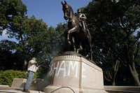 "Tino Banda with the Dallas Park and Recreation Department used a power washer to remove the spray-painted word ""SHAME"" from a statue of Gen. Robert E. Lee at Lee Park in June 2015.(File Photo)"